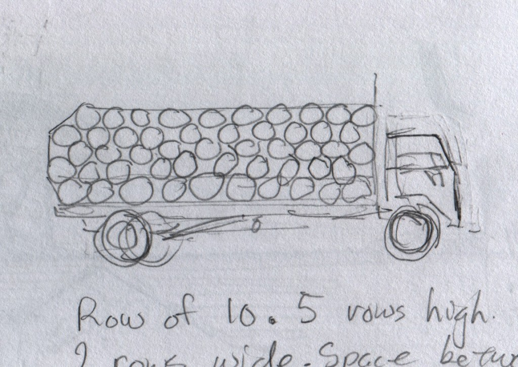 This truck carries over 100 oil barrels. The barrels are stacked five layers deep in rows of ten on each side of the truck bed. More barrels fill the space between the stacks of barrels. Ropes hold the barrels in place.